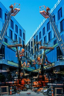 Abstract – workmen on cherry pickers installing a facade on city buildings