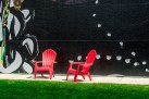 Graphic – red plastic chairs in front of wall mural