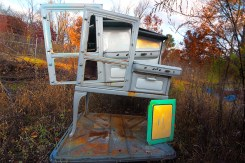 Abstract – 1920's gas stove stands alone in a grassy field