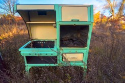 Man-Made – green and cream colored 1920's gas stove stands alone in a grassy field