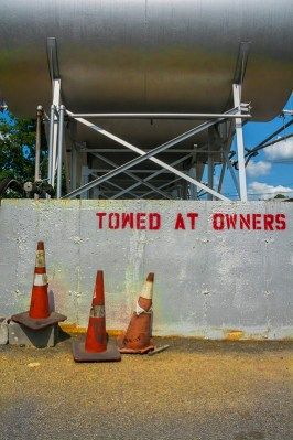 Man-made – orange cones guard parking near oil tanks