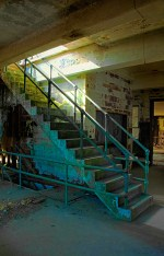 Graphic – stark, dark concrete stairway rises to light