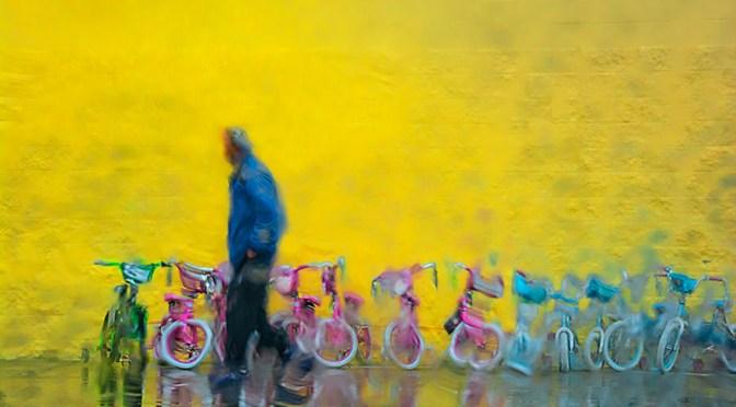 Conceptual - wet man walks past line of children's bicycles in the rain