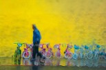 Conceptual - wet man walks past line of children's bicycles in the rain