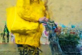 Abstract – wet woman with matching bag and raincoat pushing shopping cart