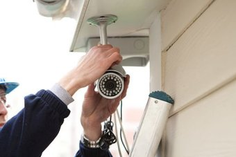 A man installs a security camera outside a home.
