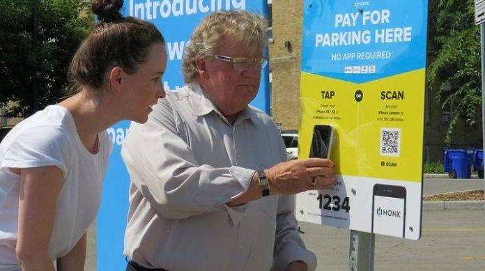 Honk Marketing Director Rachel Lemkow looks on as London Mayor Ed Holder uses the new HonkTAP to pay for parking, July 11, 2019. (Photo by Miranda Chant, Blackburn News.)