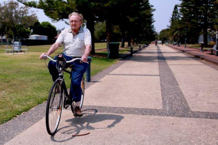 Desmond White rides a bike in a park in Newcastle.