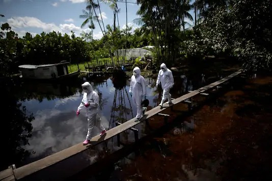 Healthcare workers Marilia Correa, 38, a nurse, Lisomar Monteiro, 38, a health secretary and Ademilton Valente, 34, a boat driver, walk along a bridge to access a house in the riverside community Pinheiro, as they visit riverside communities to check on residents during the coronavirus disease (COVID-19) outbreak, in the municipality of Portel, on Marajo island, Para state, Brazil, June 6, 2020. REUTERS/Ueslei Marcelino