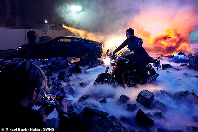 Bond in the making:The explosive photos feature Lashana in one of her costumes from the film, with all the 007 trimmings, including an Aston Martin DBS Superleggera and a Triumph Thruxton RS motorcycle
