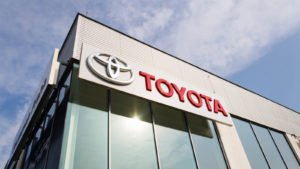 Toyota (TM) logo on the building of a dealership during daylight