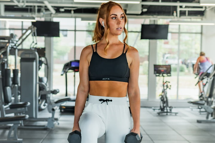 A woman in fitness attire stands in a gym holding dumbbells and wearing Apple AirPods.