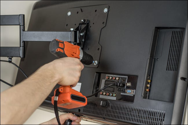 Scewing a TV in to a VESA mount.