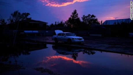 A damaged car sits beside floodwaters in the aftermath of Hurricane Ida in Jean Lafitte, La.
