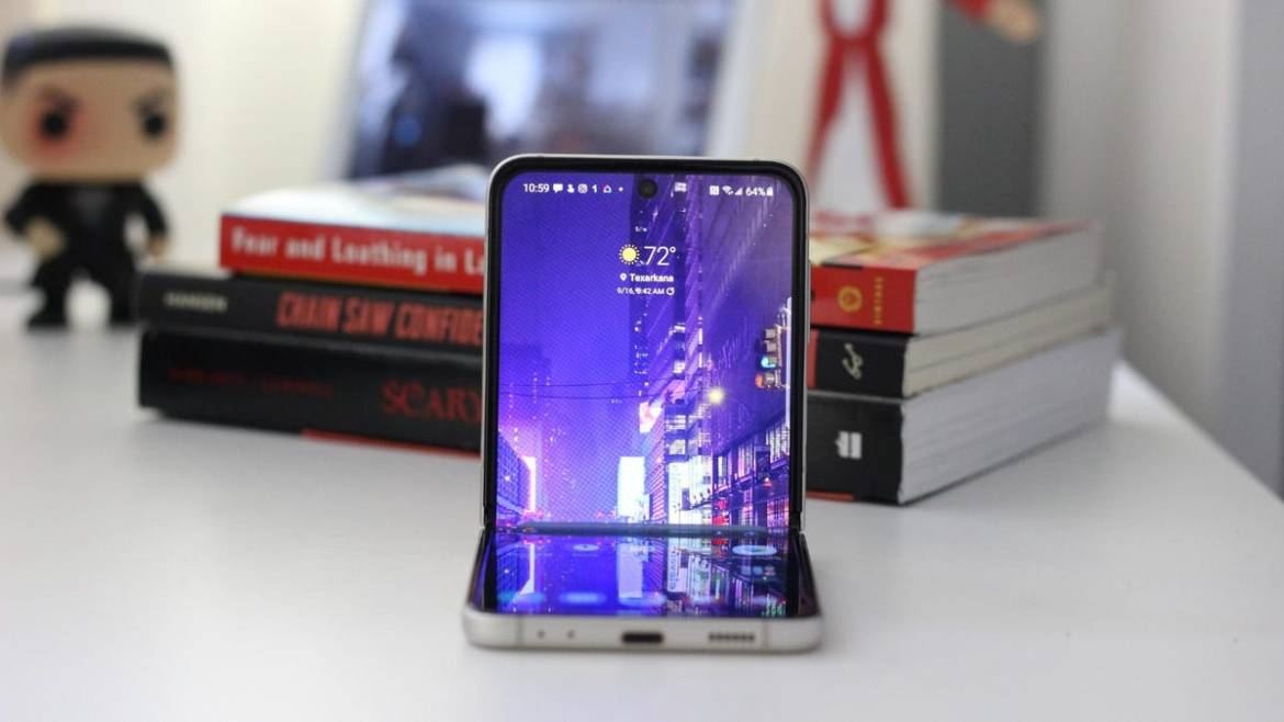 The Galaxy Z Flip 3 opened on a desk, books in the background
