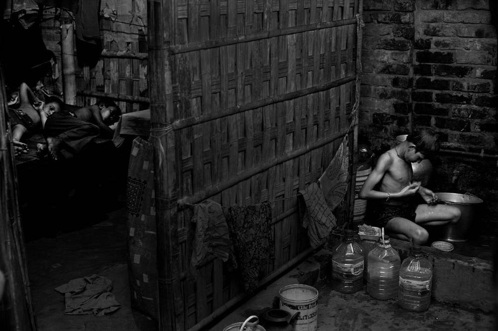 """© Md Shahnewaz Khan from the series """"Fallen Stars""""; Rubel (12) washes his body when he back home after finish work on aluminum factory. Slum in Chittagong, Bangladesh, 2013"""