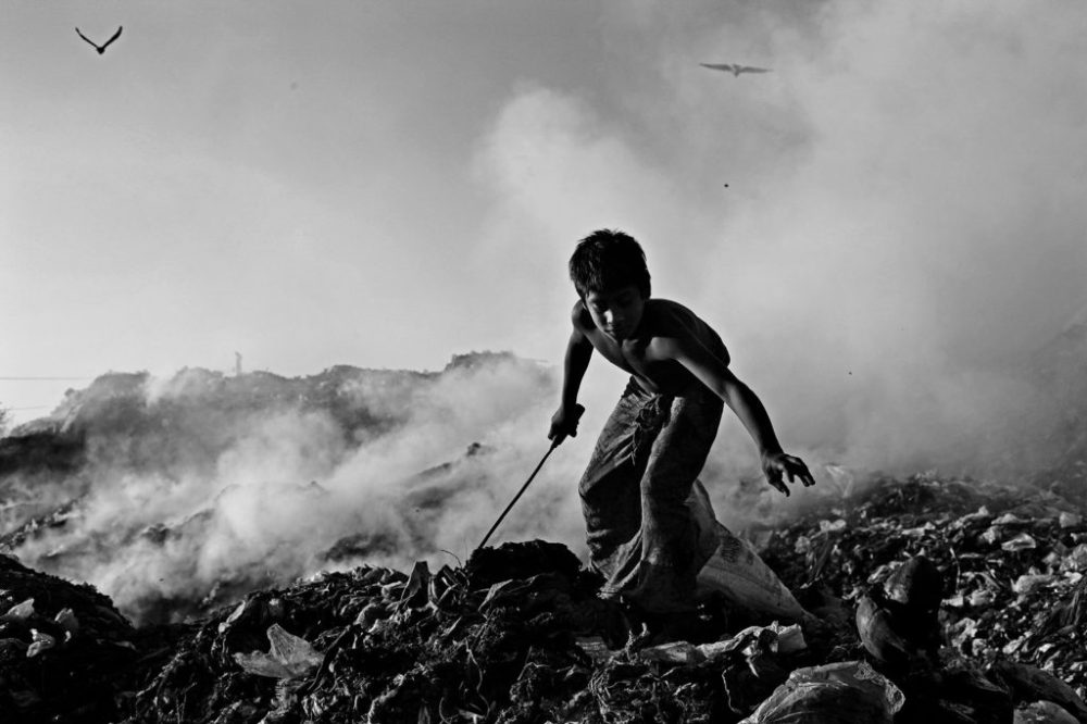 "© Md Shahnewaz Khan from the series ""Fallen Stars""; Jamal busy collecting scrap plastic and metal in hazardous condition at Anandabazar dump yard, in Chittagong, Bangladesh, 2013"