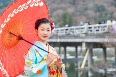 嵐山の渡月橋を背景に赤い和傘を持つ、着物を着た少女の写真