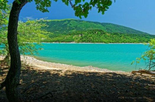 Sur la plage du lac de Monteynard-Avignonet. Ce lac de barrage (sur le cours du Drac) surprend par la couleur de ses eaux turquoises. Il est également apprécié des amateurs de sports aquatiques (notamment véliplanchistes), car il est souvent venté. Isère, France