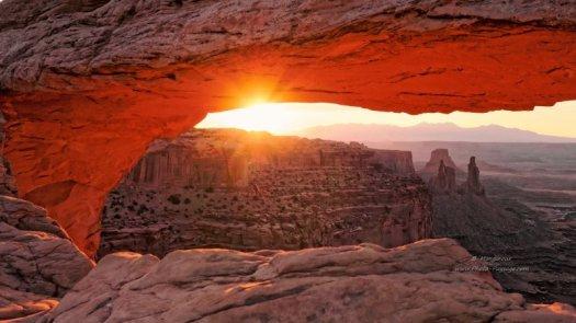 Les rayons du lever de soleil embrasent la voûte de la Mesa Arch. En arrière plan, paysage désertique du grand ouest,  falaises et pics, dans le parc National de Canyonlands, Utah, USA