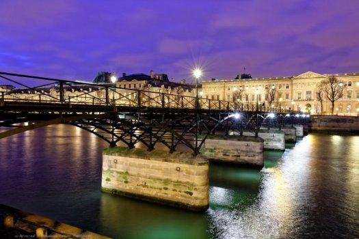 La Seine et le Pont des Arts photographiés peu après la tombée de la nuit. En arrière-plan, le palais du Louvre. Paris, France