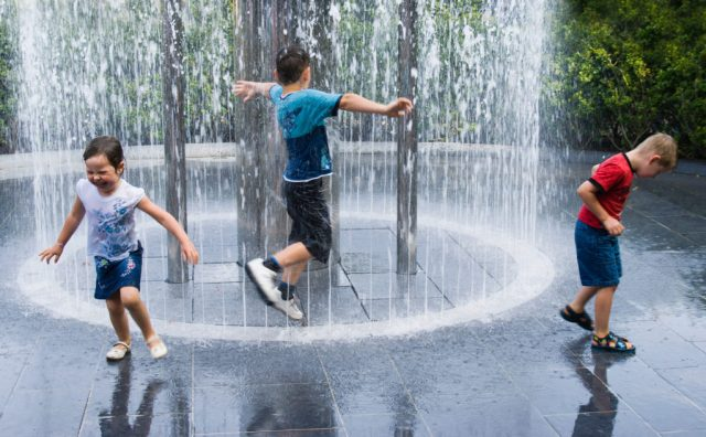 Children run into a fountain released by build up of a head of water visible in a tube popular water feature in Alnwick Garden Northumberland UK