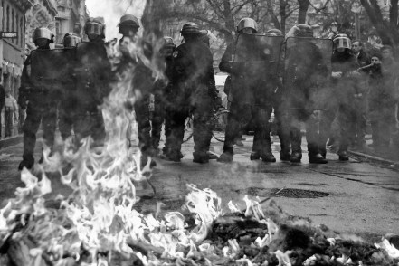 Police forces approach a burning barricade