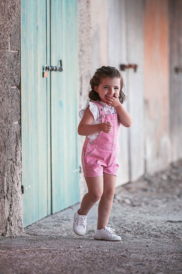 Reportaje fotográfico de ropa infantil con niña vestida con peto rosado jugando en embarcadero de Ibiza