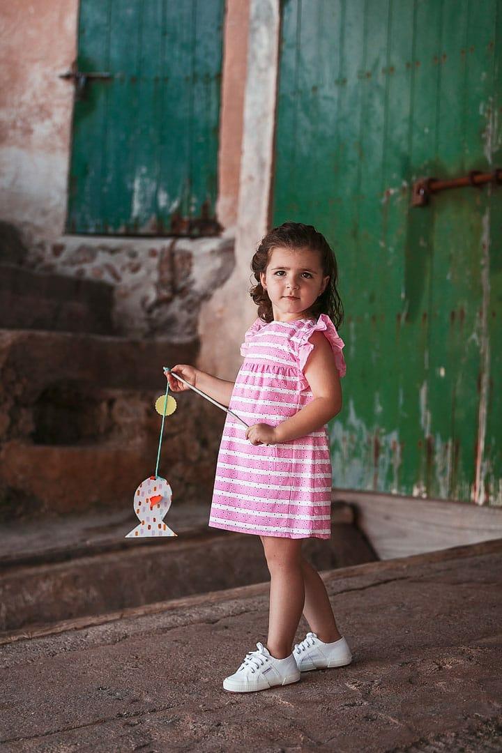 Reportaje fotográfico de ropa infantil con niña vestida con vestido rosado en embarcadero de Ibiza