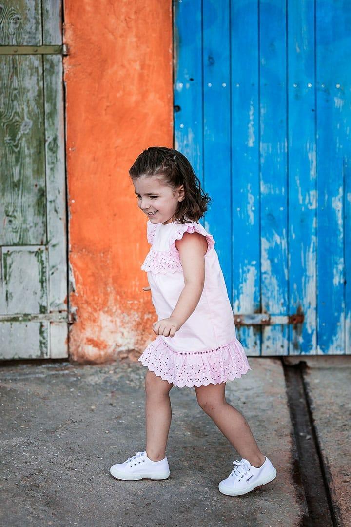 Reportaje fotográfico de ropa infantil con niña vestida con vestido rosado jugando en embarcadero de Ibiza