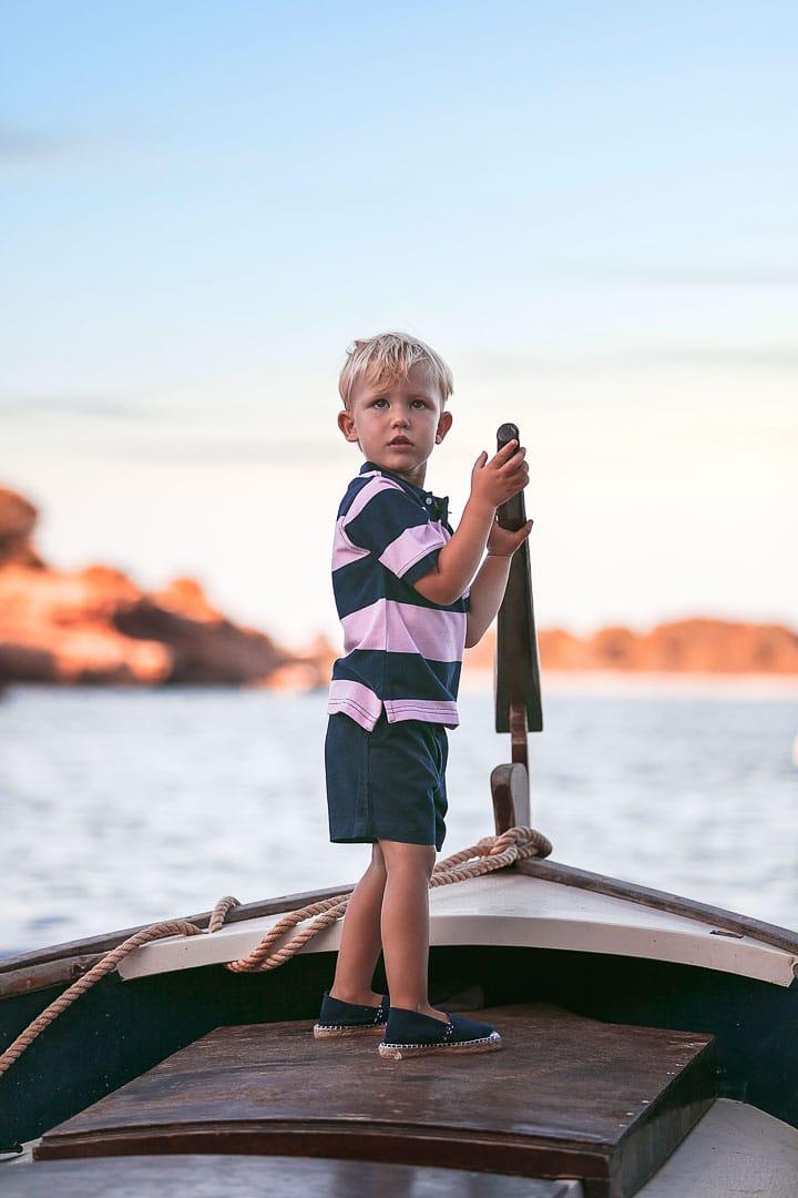 Retrato de un niño sonriente jugando sobre una barca vestido con camiseta rayada de color azul y pantalón azul en embarcadero de Ibiza