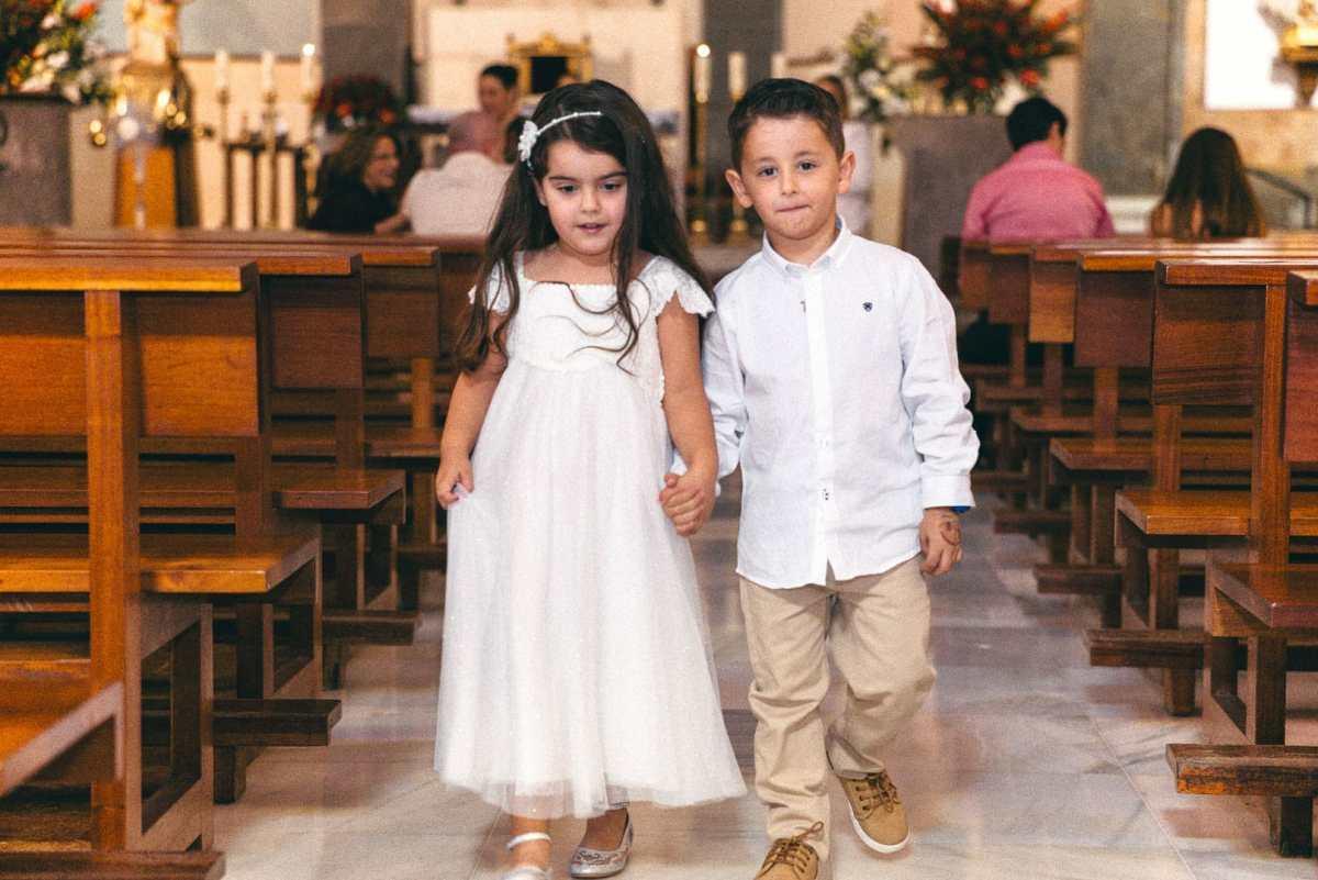 foto de dos primos cogidos de la mano y andando hacia la salida de la iglesia de san rafael