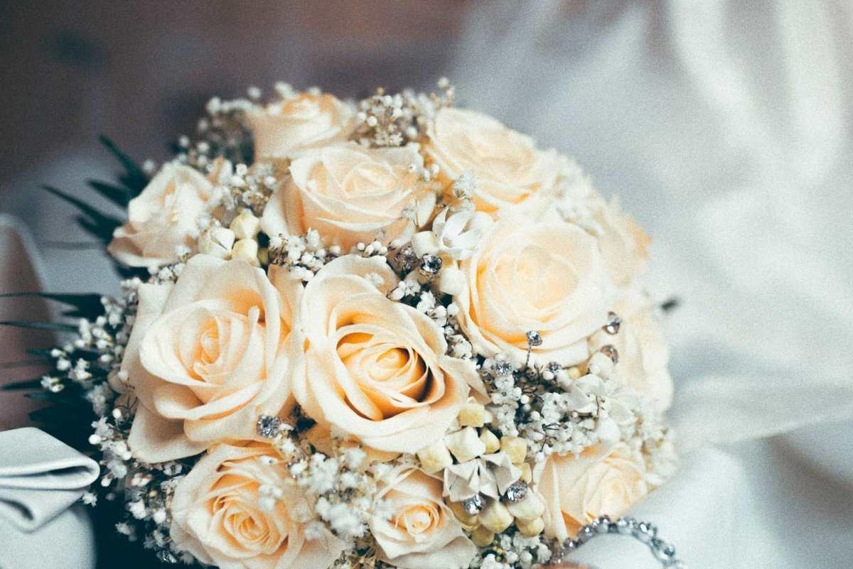 fotografia de detalles florales de rosas sobre una cama con el vestido y los zapatos