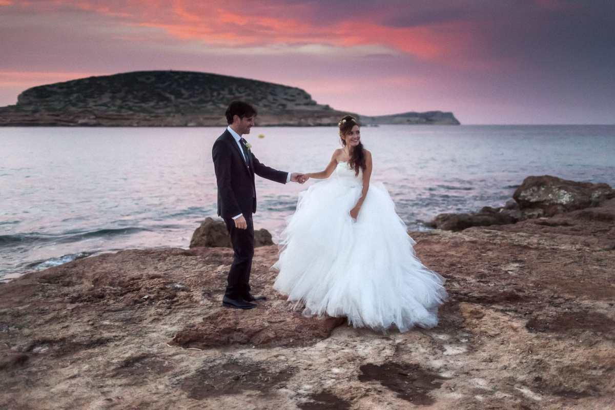 fotografia postboda al atardecer de recien casados cogidos de la mano y felices en cala comte
