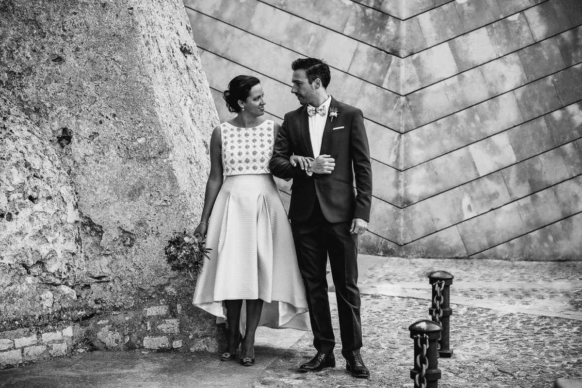 retrato fotografico de postboda de pareja recien casados paseando agarrados del brazo y mirandose en las calles de la muralla de dalt vila en ibiza baleares