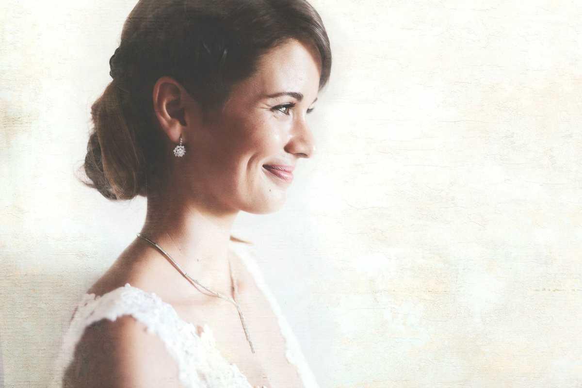 retrato fotografico lateral de novia sonriendo con fondo blanco en ibiza