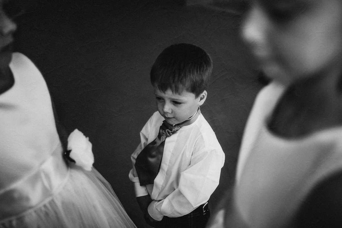 retrato instantaneo en blanco y negro del hijo de los novios con pajarita y blusa alrededor de sus primas en ibiza