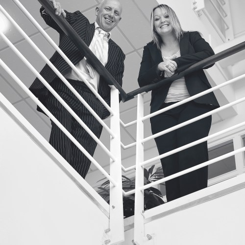 Man & lady in business suits looking down over balcony black & white - People photography