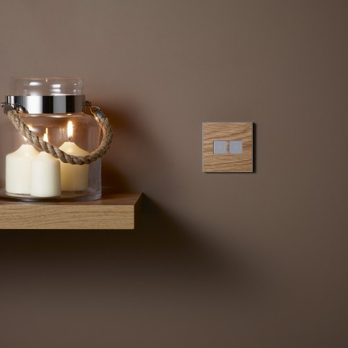 Wooden shelf with storm jar of lit candles again taupe wall and wooden effect MK Dimensions switch electrical photography