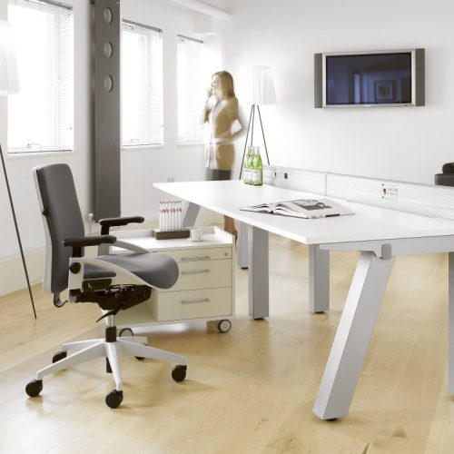 White desk, black chair in office lady speaking onphone in background with movement - Furniture photography