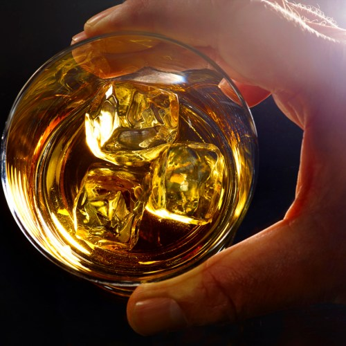 Male hand holding a glass of whiskey and ice, backlit - Food and drink photography