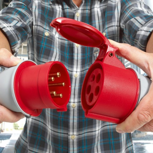 Man wearing check shirt, pulling apart red commando socket electrical photography