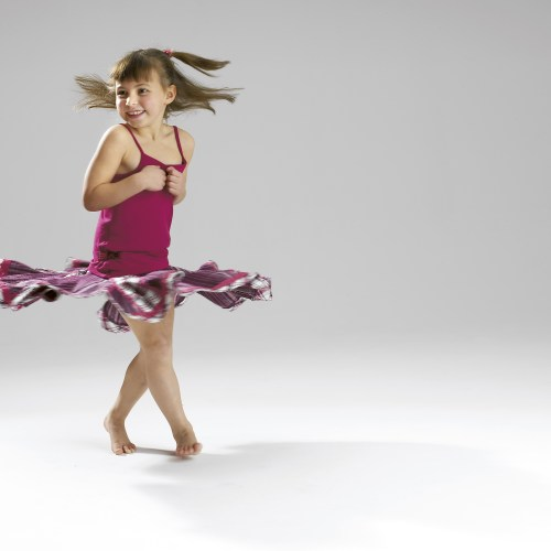 Little girl spinning around with her skirt twirling around, studio shot - People photography