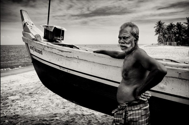 A Kerala Fisherman with his boat on the Southern India coast beaches near Kovalam