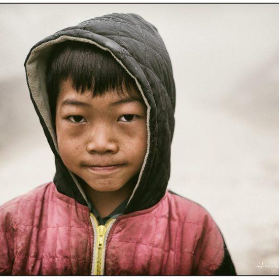 school boy in the rain near sapa vietnam