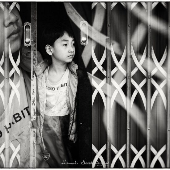 small boy in a doorway at the chinese border with vietnam