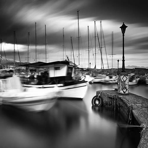 Boats in the harbor rock back and forth with the tide - black and white long exposure by Vassilis Tangoulis