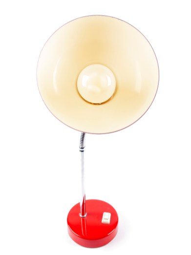 An old vintage red desk lamp with a light bulb