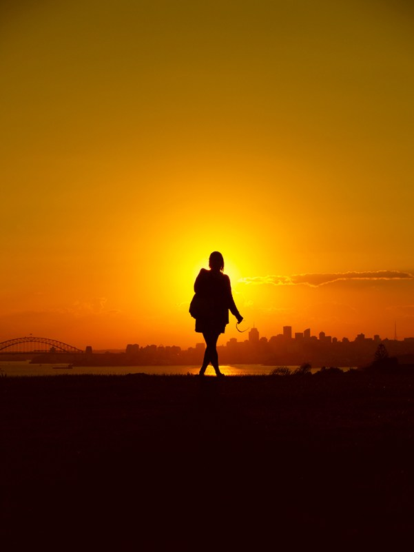 Sunset over Sydney, Australia with a woman standing in front of the sun enjoying the view