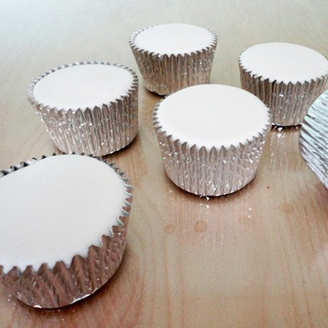 6 cupcakes iced white on the top in silver cases
